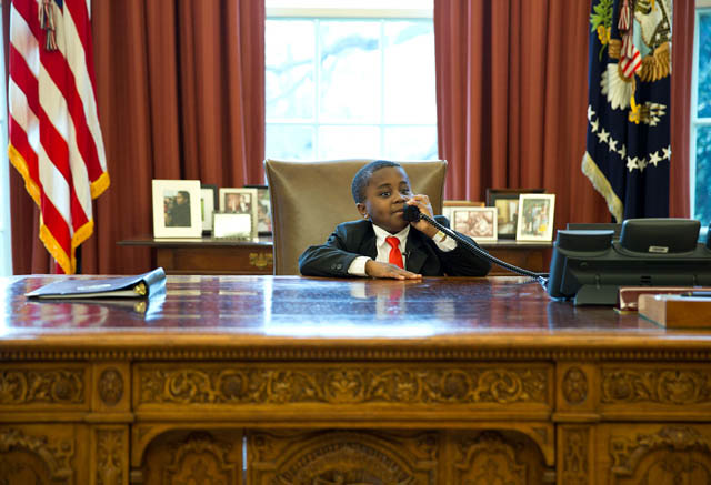 """Robby Novak, AKA 'Kid President', feigns a phone call at the Resolute Desk during his visit to see the President in the Oval Office."""