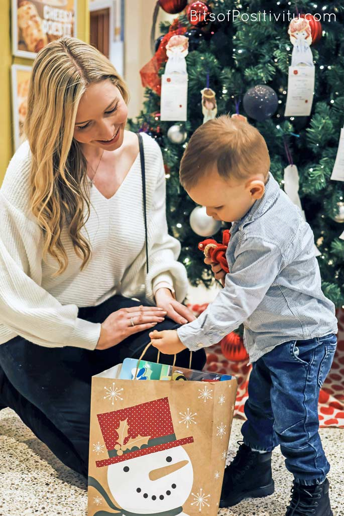 Mom and Toddler with Kindness Elves and Gift Bag for a Toddler