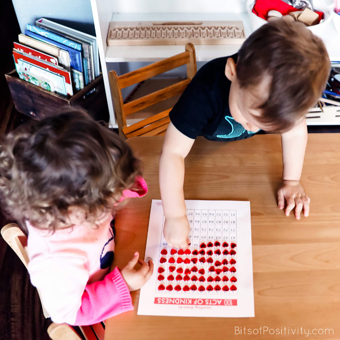 Toddler Cousins Putting Their Heart Stickers on Our Family 100 Acts of Kindness Chart